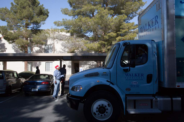 Walker delivery man Joseph Wayman waits as the Walker Furniture truck arrives at the home of Michael Howard and Octavia Haney in east Las Vegas on Friday, Dec. 13, 2013. Every year Walker Furnitur ...