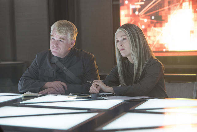 Plutarch Heavensbee (Philip Seymour Hoffman) and President Coin (Julianne Moore) in THE HUNGER GAMES: MOCKINGJAY – PART 1. Photo Credit: Murray Close LIONSGATE