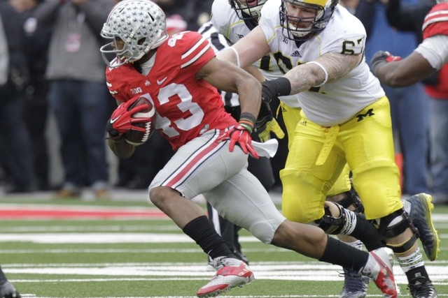 Ohio State linebacker Darron Lee, left, picks up a fumble in front of Michigan linemen Ben Braden, center, and Kyle Kalis and returns it for a touchdown during the fourth quarter of an NCAA colleg ...