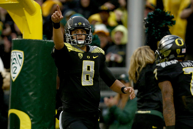 Oregon quarterback Marcus Mariota (8) points to the crowd after scoring a touchdown during the first quarter against Stanford in an NCAA college football game in Eugene, Ore., Saturday, Nov. 1, 20 ...