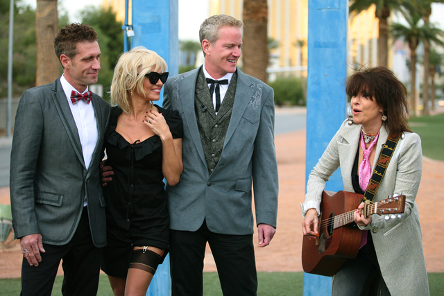 Jack Ryan, from left, actress Pamela Anderson, and Dan Mathews, senior vice president of PETA, are serenaded by rock icon Chrissie Hynde after the wedding ceremony of Ryan and Mathews at the Welco ...