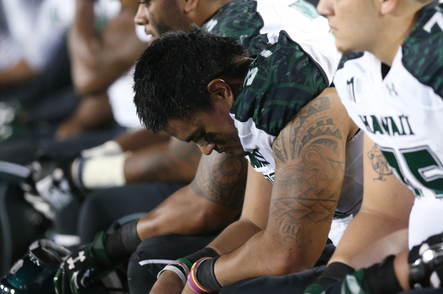 Hawaii linebacker Simon Poti hangs his head as he sits on bench as time runs out in Colorado State's 49-22 victory over Hawaii in an NCAA college football game in Fort Collins, Colo., on Saturday, ...