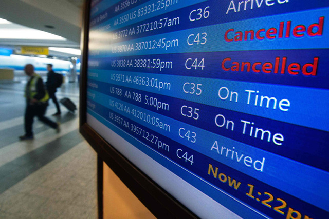 People walk past a sign board that announces cancelled flights at LaGuardia airport on the day before Thanksgiving, in New York November 26, 2014. A storm expected to blast the East Coast with rai ...