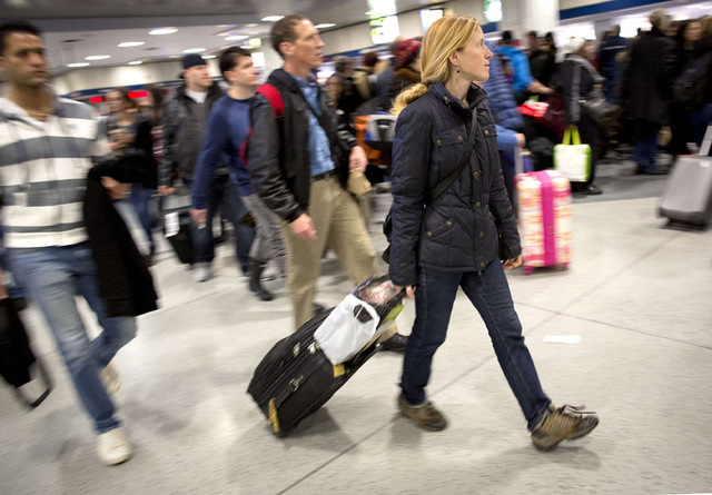 Holiday travellers walk through Penn Station in New York, November 26, 2014. A blast of rain and snow along the East Coast is threatening to snarl traffic and disrupt flights for millions of Ameri ...