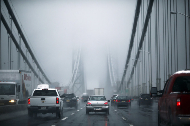Cars make their way through the Washington bridge in New York November 26, 2014. A storm expected to blast the East Coast with rain and snow through Thursday morning is threatening to snarl traffi ...