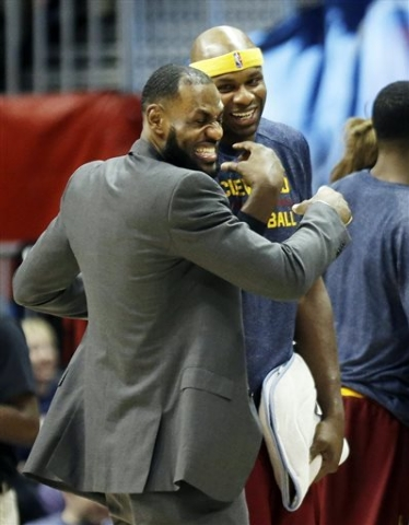 Cleveland Cavaliers' LeBron James, left, stands with teammate Brendan Haywood during a timeout in the second quarter of an NBA basketball game against the Atlanta Hawks, Tuesday, Dec. 30, 2014, in ...