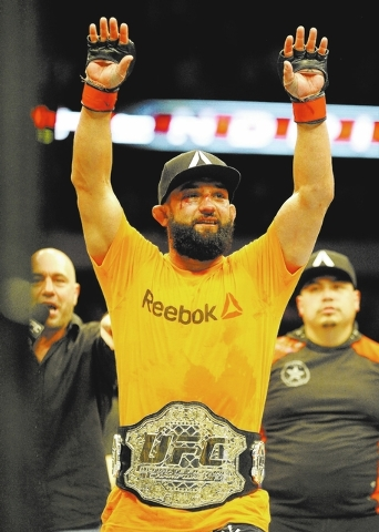 Johny Hendricks celebrates after beating Robbie Lawler during a UFC 171 mixed martial arts welterweight title bout, Saturday, March 15, 2014, in Dallas. Hendricks won by decision. (AP Photo/Matt S ...