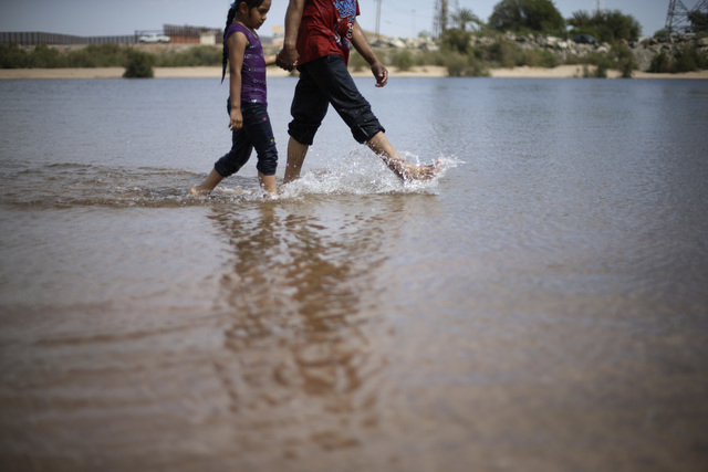 Salvador Herrera walks with his daughter Cristina in Colorado river water flowing in a normally dry riverbed Thursday, March 27, 2014, in San Luis Rio Colorado, Mexico. Colorado River water has be ...