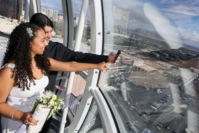Daisy and Michael Hurtado take a photo of themselves after participating in a vow renewal ceremony on The High Roller Saturday, Dec. 13, 2014, in Las Vegas. The High Roller offered free in-cabin w ...