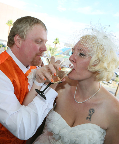 Jeremy Cardon, left, and his bride Angel Dodson, of Colorado Springs, drink champagne after getting married on The High Roller Saturday, Dec. 13, 2014, in Las Vegas. The High Roller offered free i ...