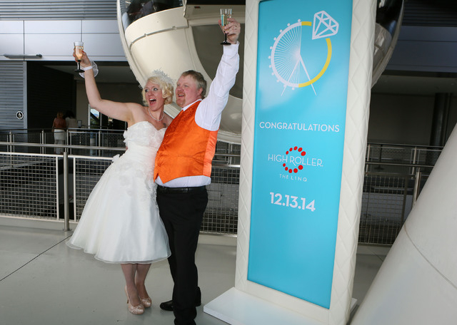 Angel Dodson, left, and her groom Jeremy Cardon, of Colorado Springs, raise their champagne glasses for a photograph after getting married on The High Roller Saturday, Dec. 13, 2014, in Las Vegas. ...