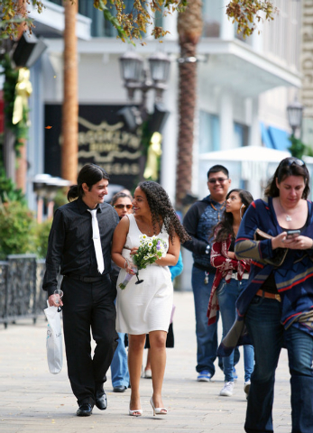 Michael Hurtado, left, and his wife Daisy walk along the boardwalk near The High Roller after participating in a vow renewal ceremony on The High Roller Saturday, Dec. 13, 2014, in Las Vegas. The  ...
