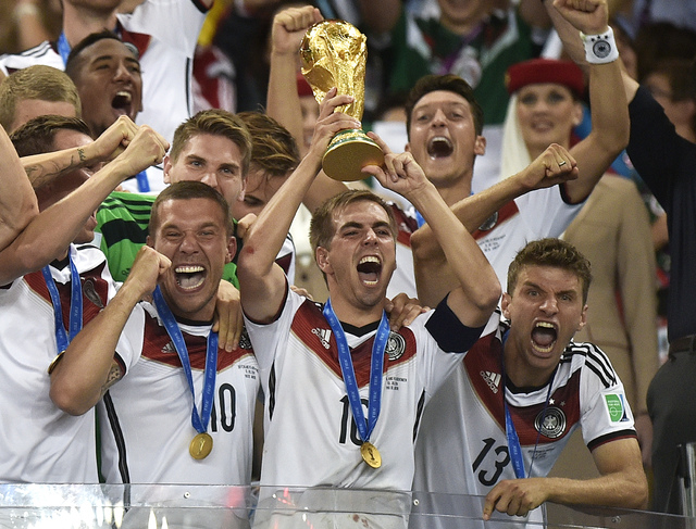 Germany's Philipp Lahm (16) raises the trophy after the World Cup final soccer match between Germany and Argentina at the Maracana Stadium in Rio de Janeiro, Brazil, Sunday, July 13, 2014. Germany ...