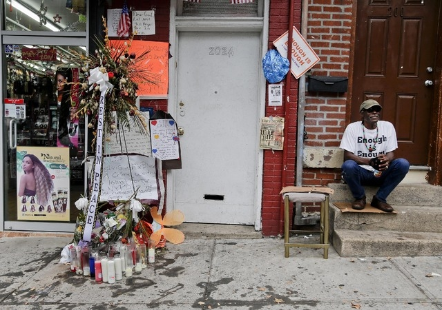 Doug Brinson sits on a stoop next to a makeshift memorial for Eric Garner, Friday, Aug. 1, 2014, in the Staten Island borough of New York. Garner died after he was put in a chokehold while being a ...
