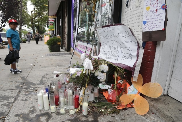A young boy stops as he passes a makeshift memorial for Eric Garner, Friday, Aug. 1, 2014, in the Staten Island borough of New York. Garner was put in a chokehold while being arrested at the site  ...