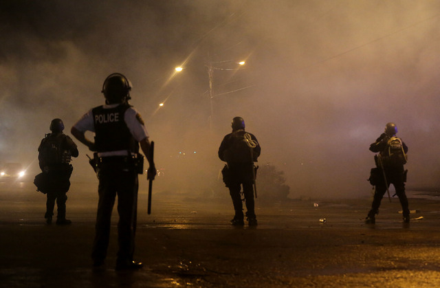 A law enforcement officer watches Sunday, Aug. 17, 2014, as tear gas is fired to disperse a crowd protesting the shooting of teenager Michael Brown on Aug. 9, 2014, in Ferguson, Mo. Brown's shooti ...