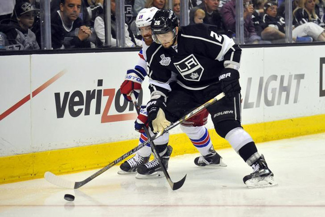 Jun 7, 2014; Los Angeles, CA, USA; Los Angeles Kings defenseman Slava Voynov (26) battles for the puck with New York Rangers center Brad Richards (19) in the second period during game two of the 2 ...