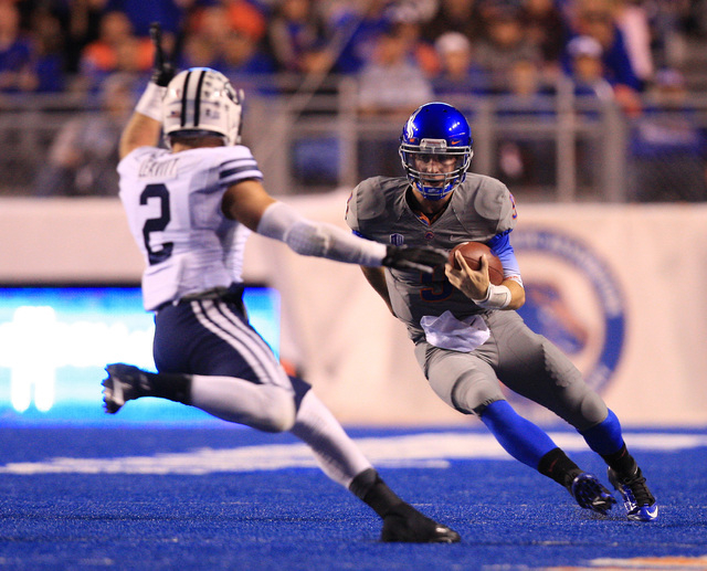 Boise State quarterback Grant Hedrick (9) is chased by Brigham Young defensive back Dallin Leavitt (2) on Oct 24, 2014. (Brian Losness-USA TODAY Sports)