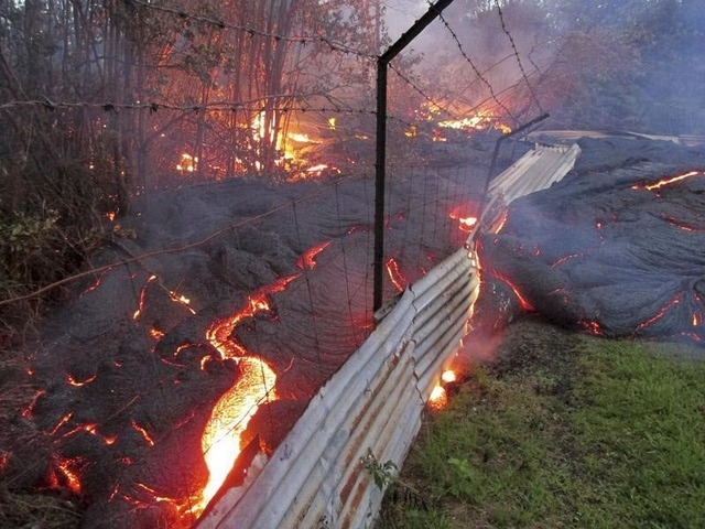 The lava flow from the Kilauea volcano moves over a fence on private property near the village of Pahoa, Hawaii in this handout picture from the U.S. Geological Survey (USGS) taken October 31, 201 ...