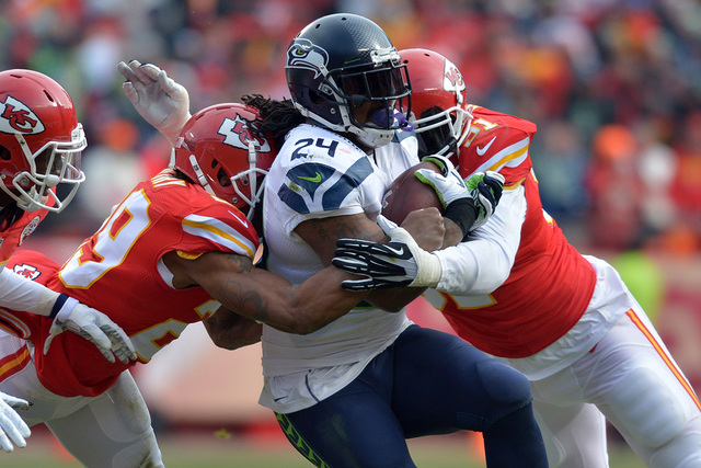Nov 16, 2014; Kansas City, MO, USA; Seattle Seahawks running back Marshawn Lynch (24) is tackled by Kansas City Chiefs outside linebacker Tamba Hali (91) and strong safety Eric Berry (29) during t ...