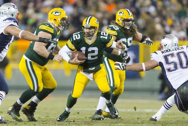Green Bay Packers quarterback Aaron Rodgers (12) scrambles with the football during the third quarter against the New England Patriots at Lambeau Field.  Green Bay won 26-21.  (Jeff Hanisch-USA TO ...