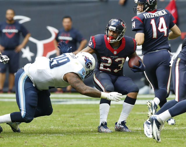 Nov 30, 2014; Houston, TX, USA; Houston Texans running back Arian Foster (23) runs with that ball against Tennessee Titans defensive tackle Jurrel Casey (99) at NRG Stadium. (Matthew Emmons-USA TO ...