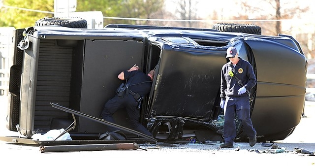 Police and fire officials examine Carolina Panthers quarterback Cam Newton's damaged truck following a crash in uptown Charlotte, North Carolina, December 9, 2014. Newton was involved in a car acc ...