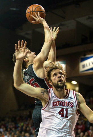 UNLV Rebels guard Cody Doolin (45) is fouled by South Dakota Coyotes forward Eric Robertson (41) during the first half at Sanford Pentagon in Sioux Falls, S.D., on Saturday, Dec. 13, 2014. (Brace  ...