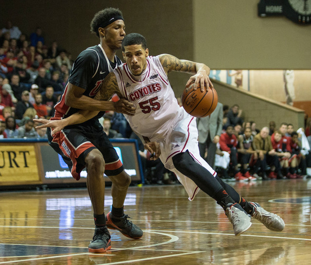 South Dakota Coyotes guard Tyler Larson (55) dribbles past UNLV Rebels guard Patrick McCaw (2) during the second half at Sanford Pentagon. UNLV defeated South Dakota  75-61 in Sioux Falls on Satur ...