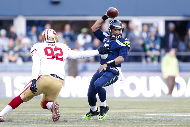 Dec 14, 2014; Seattle, WA, USA; Seattle Seahawks quarterback Russell Wilson (3) eludes a sack by San Francisco 49ers nose tackle Quinton Dial (92) during the second quarter at CenturyLink Field. ( ...