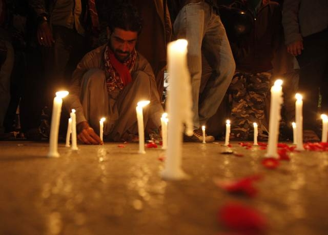 A man lights candles to mourn the victims from the Army Public School in Peshawar, which was attacked by Taliban gunmen, in Karachi, Tuesday, Dec. 16, 2014. Taliban gunmen in Pakistan took hundred ...