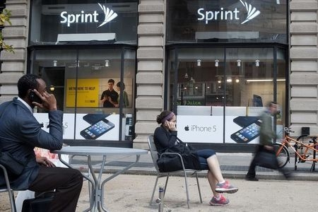 People talk on their cell phones as passers-by walk past a Sprint store in New York. The U.S. Consumer Financial Protection Bureau on Wednesday, Dec. 17, 2014, filed a lawsuit against Sprint Corp. ...
