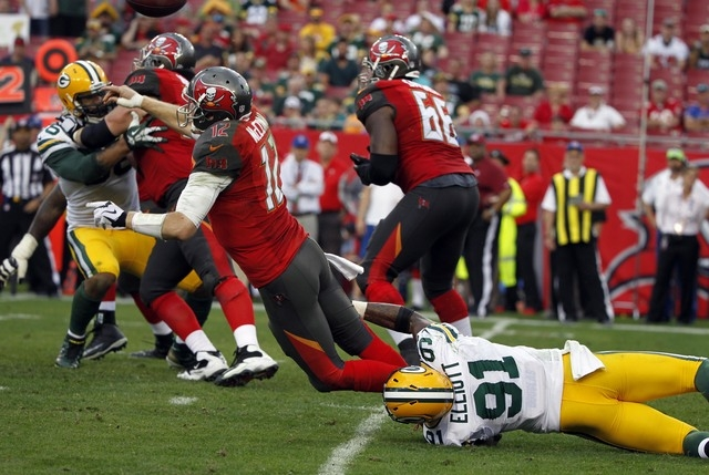 Tampa Bay comes into the final game of the season with just two winns. On Dec. 21, Buccaneers quarterback Josh McCown (12) gets rid of the ball while being tripped up by Green Bay linebacker Jay E ...