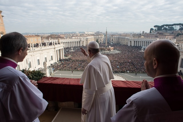 """Pope Francis waves as he delivers a """"Urbi et Orbi"""" (to the city and world) message from the balcony overlooking St. Peter's Square at the Vatican December 25, 2014.  (Osservatore Romano/Reuters)"""