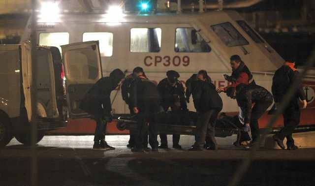 Italian Coast Guard members carry a body as they arrive in the Brindisi harbour December 28, 2014. Italian and Greek helicopter crews prepared to work through the night to airlift passengers in pa ...