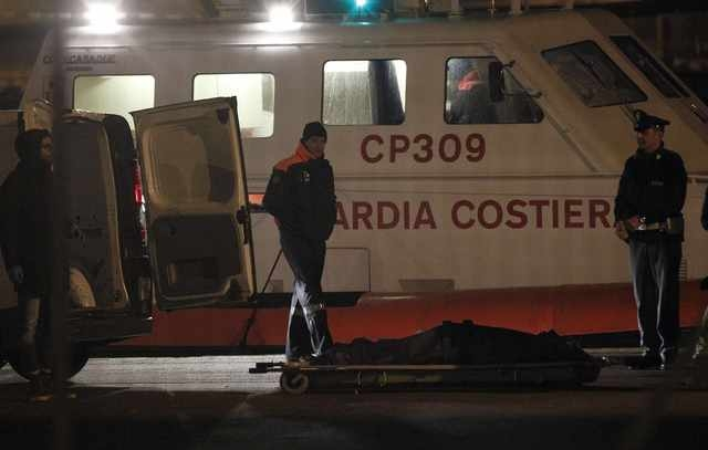 Italian Coast Guard members stand next a body as they arrive in the Brindisi harbour December 28, 2014. Italian and Greek helicopter crews prepared to work through the night to airlift passengers  ...