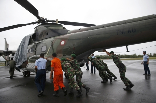 Military personnel move an Indonesian military helicopter used in recovery efforts for the missing AirAsia plane, as it sits idle due to bad  weather, on the tarmac of Iskandar Airport in Pangkala ...