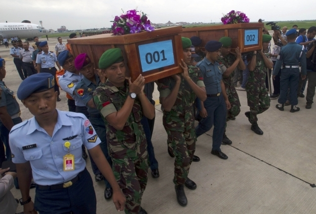 Indonesian military carry the caskets containing the bodies of two AirAsia flight QZ8501 passengers recovered off the coast of Borneo at a military base in Surabaya, Wednesday, Dec. 31, 2014. Indo ...