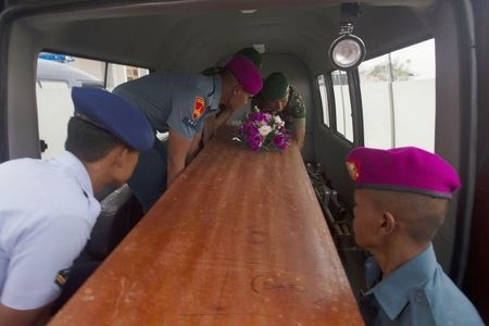 Indonesian military load a casket containing the body of an AirAsia flight QZ8501 passenger recovered off the coast of Borneo into a vehicle at a military base in Surabaya, Wednesday, Dec. 31, 201 ...