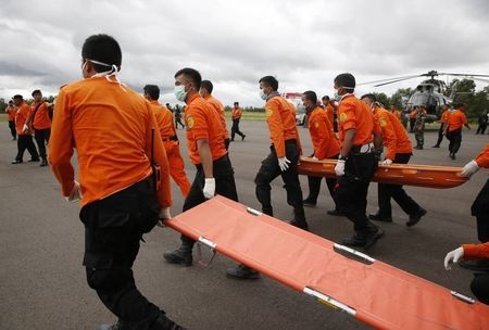 Indonesian Search and Rescue crews walk out to meet a helicopter carrying the bodies of two AirAsia passengers recovered from the sea, at Iskandar airport in Pangkalan Bun, Central Kalimantan, Wed ...