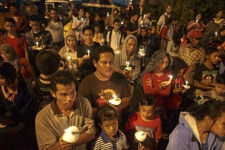 Indonesians hold up candles during a candle light vigil for the victims of AirAsia flight QZ8501 at Surabaya, Wednesday, Dec. 31, 2014. (Reuters/Athit Perawongmetha)