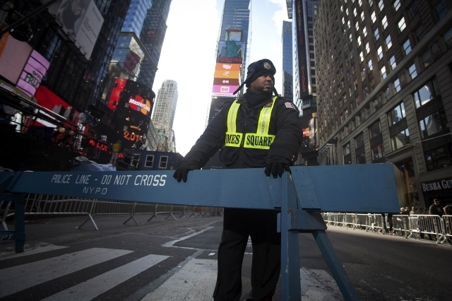 A security guard stands in Times Square as streets are closed in preparation for New Year's Eve celebrations in New York, Wednesday, Dec. 31, 2014. (Reuters/Carlo Allegri)