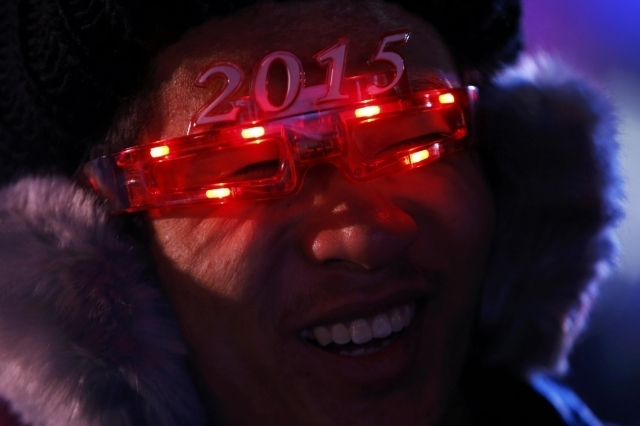 "A man wears a pair of eyewear in the shape of the year 2015 as he waits for a countdown event to celebrate the arrival of the new year in front of the National Stadium, also known as the ""Bird's N ..."