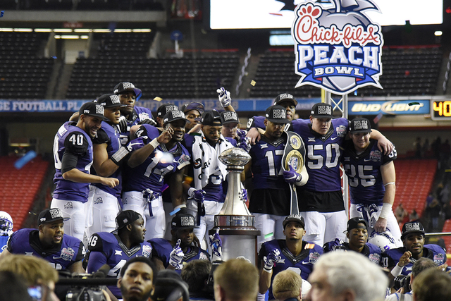 Dec 31, 2014; Atlanta , GA, USA; TCU Horned Frogs team members pose for a photo with the trophy after the 2014 Peach Bowl against the Mississippi Rebels at the Georgia Dome. TCU defeated Ole Miss  ...