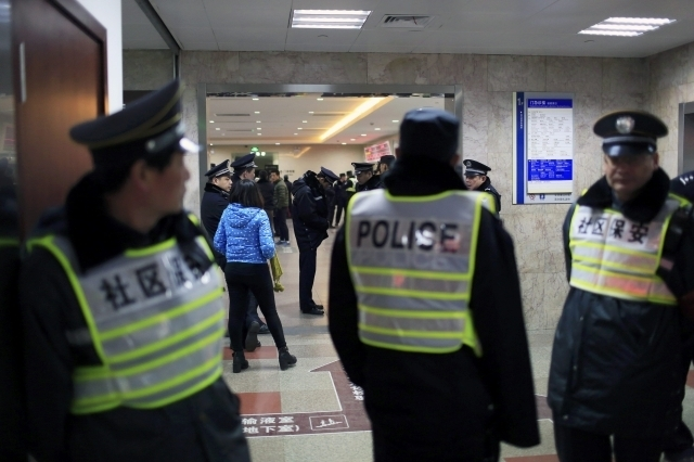 Security personnel (front) and policemen stand next to an entrance to a hospital where injured people of a stampede incident are treated, in Shanghai, Thursday, Jan. 1, 2015. At least 35 people we ...