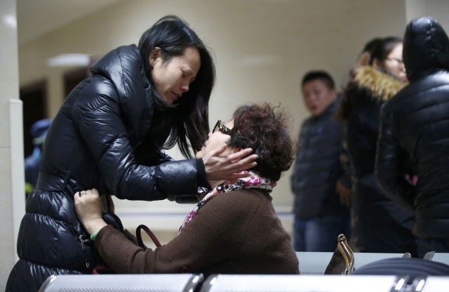 Relatives of a victim hug as they wait at a hospital where injured people of a stampede incident are treated in Shanghai, Thursday, Jan. 1, 2015. At least 35 people were killed and 42 were injured ...