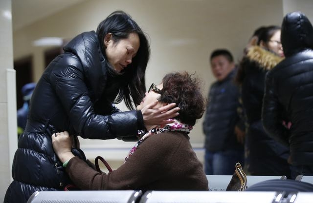 Relatives of a victim hug as they wait at a hospital where injured people of a stampede incident are treated in Shanghai January 1, 2015. At least 35 people were killed and 42 were injured in a st ...