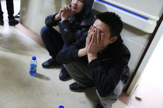 A friend of a victim covers his face as he waits outside a hospital where injured people of a stampede incident are treated, in Shanghai January 1, 2015. REUTERS/Aly Song