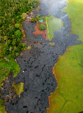In this Oct. 28, 2014 photo provided by Pete Stachowicz of Paradise Helicopters, lava flow has partially buried a cemetery, top center, near the town of Pahoa on the Big Island of Hawaii. The Nati ...