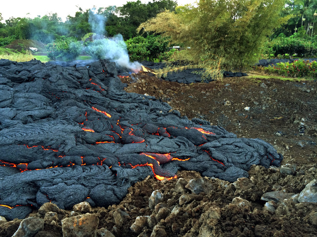 This Oct. 30, 2014 photo from the U.S. Geological Survey shows a breakout of lava oozing from the margin of the lava flow near the town of Pahoa on the Big Island of Hawaii. These breakouts are lo ...